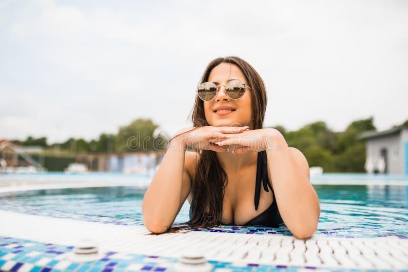 在游泳池边缘的美丽的妇女 免版税图库摄影