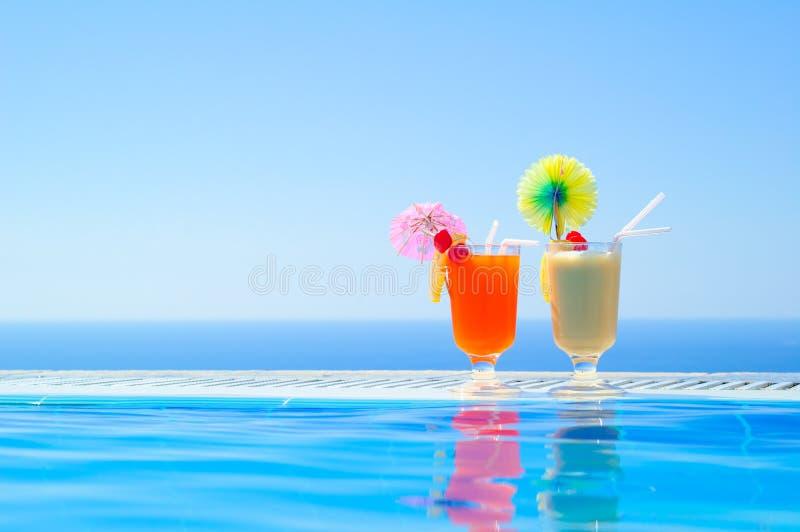 在游泳池附近的两个五颜六色的热带鸡尾酒在温暖的蓝色海背景  异乎寻常的暑假 图库摄影