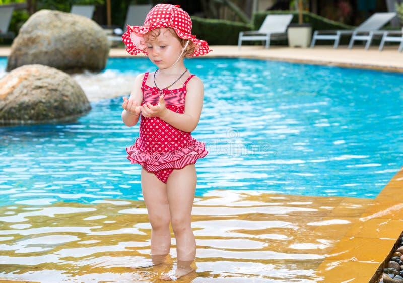 在游泳池附近的滑稽的小孩女孩在热带手段在泰国,普吉岛 免版税库存图片