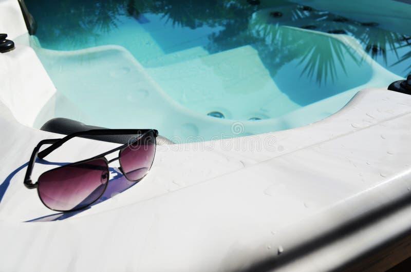 在游泳温泉水池边缘的太阳镜  库存图片