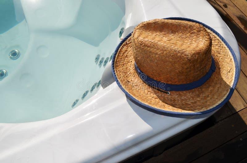 在游泳温泉水池边缘的帽子  库存图片
