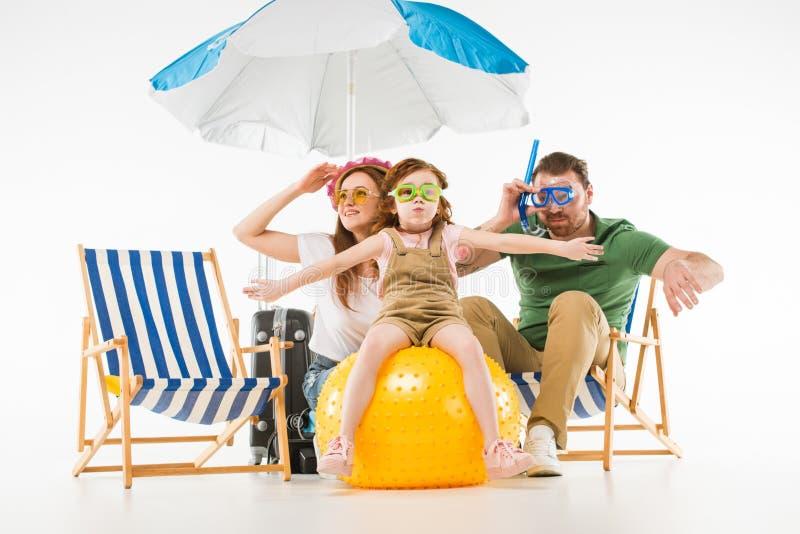 在游泳的风镜的家庭与遮光罩太阳懒人和球 免版税库存图片