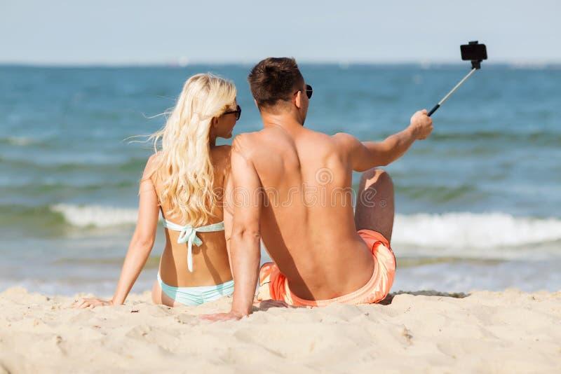 在游泳衣的愉快的夫妇坐夏天靠岸 免版税库存照片