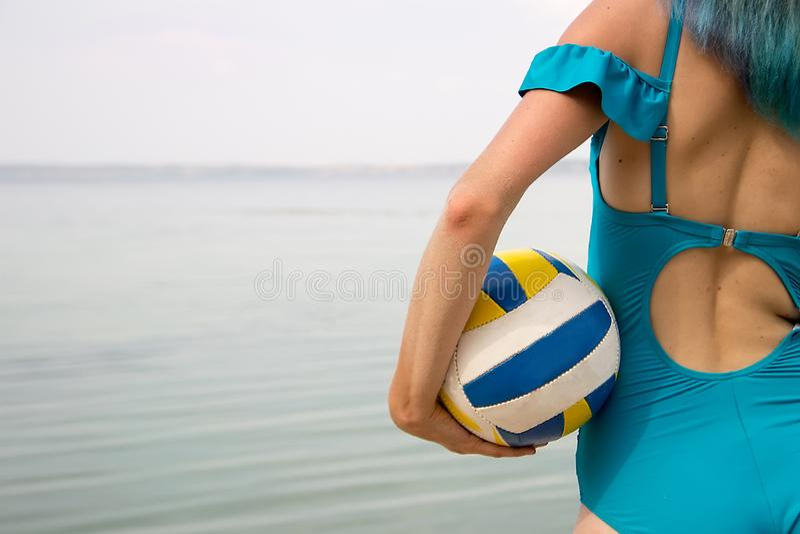 在游泳衣,有volleyb的色的头发的美好的女性后面 免版税图库摄影