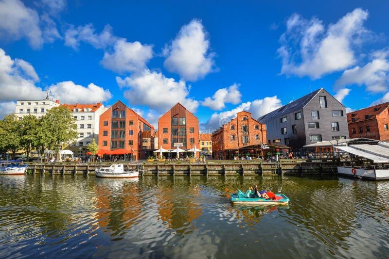 在游船、丹麦人河、堤防和红砖的美丽的景色安置克莱佩达,立陶宛 免版税库存图片