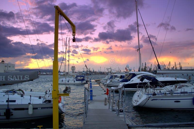 在游艇口岸的紫罗兰色日落地平线 图库摄影