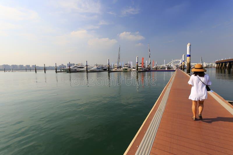 在游艇小游艇船坞木板走道的妇女步行  免版税库存照片