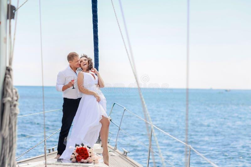 在游艇的一对已婚夫妇 愉快的新娘和新郎在他们的婚礼那天 图库摄影