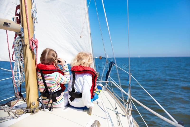 在游艇的孩子风帆在海 在小船的儿童航行 库存照片