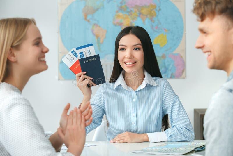 在游览机构通信的年轻夫妇与拿着文件的旅行代理人旅行的概念 免版税图库摄影