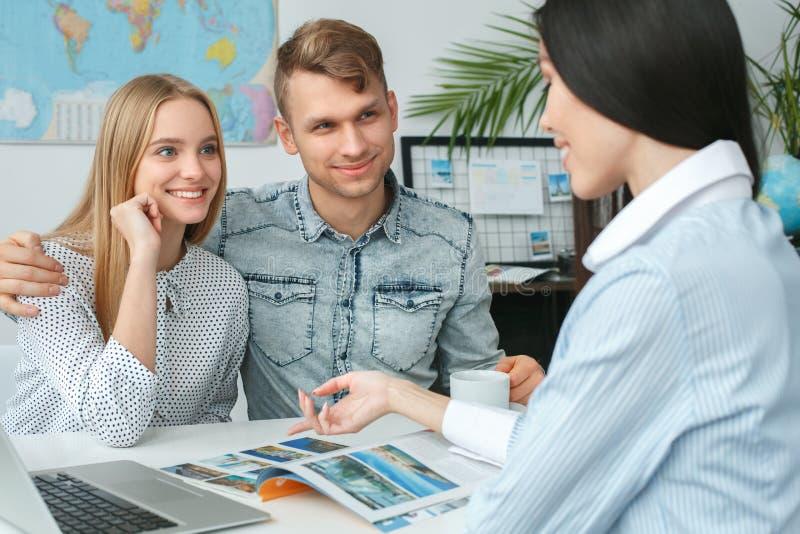 在游览机构通信的年轻夫妇与旅行代理人移动的概念游览目的地 免版税库存图片
