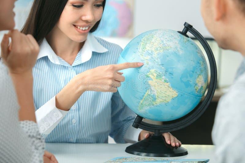 在游览机构通信的年轻夫妇与选择国家的旅行代理人旅行的概念地球 免版税库存照片