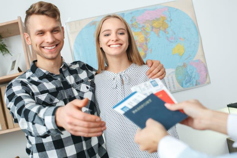 在游览机构通信的年轻夫妇与采取文件的旅行代理人旅行的概念 图库摄影