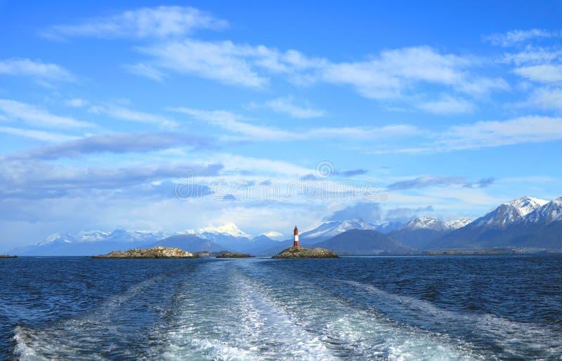 在游轮船尾的起泡沫的水与列斯Eclaireurs灯塔和雪的加盖了在距离,乌斯怀亚的山脉 库存图片