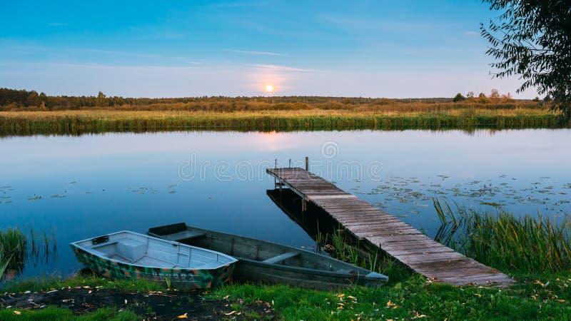 在湖、河和划船渔船镇静水的木板码头  免版税库存照片