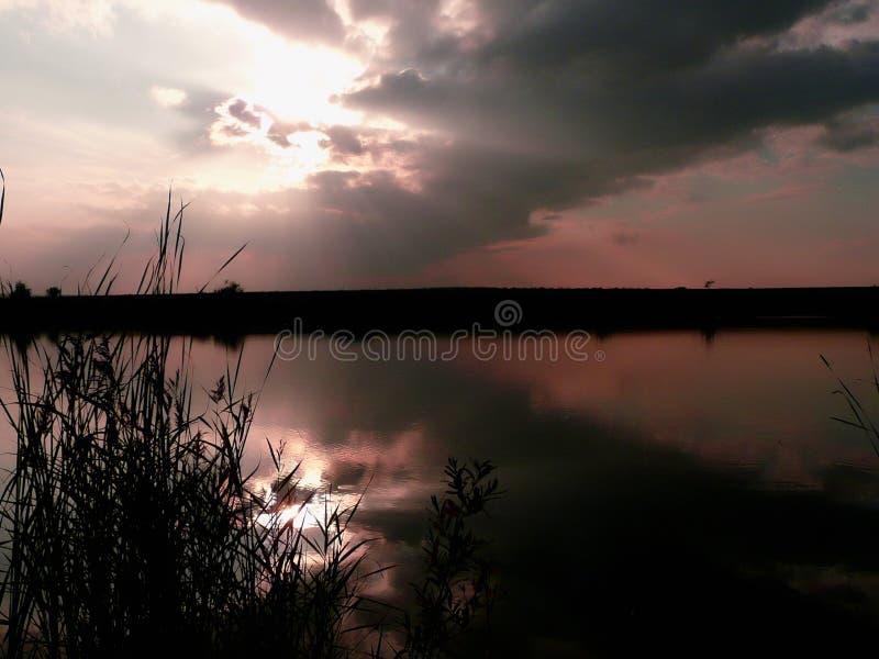在湖、雷云和草的日落在岸 图库摄影