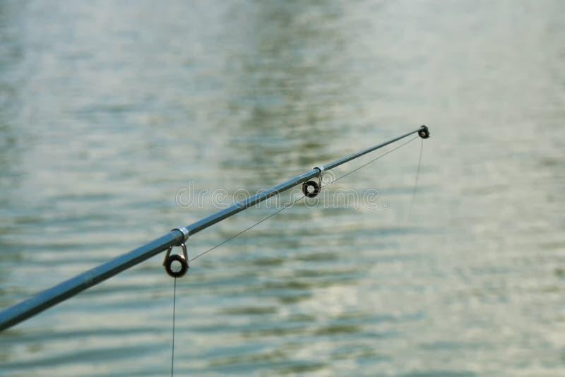 在湖上的钓鱼竿特写镜头有模糊的水背景 免版税库存图片
