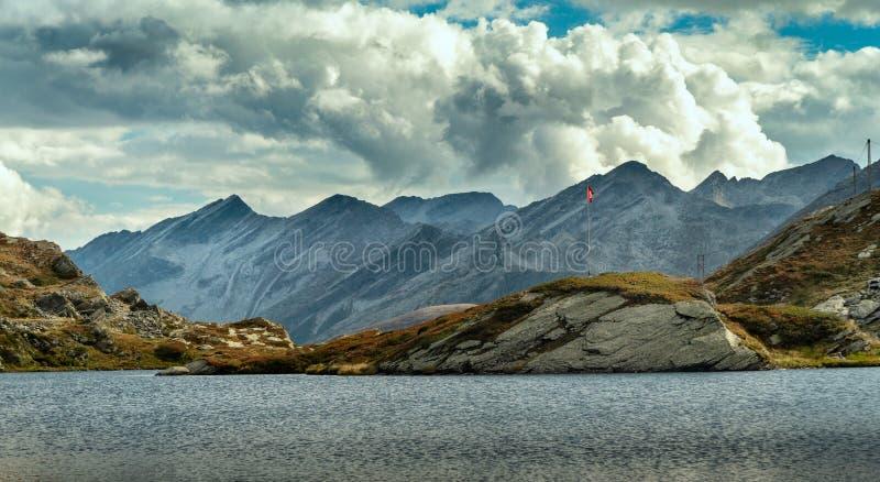 在湖中间的一点海岛有瑞士旗子的 库存图片