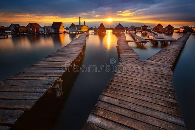 在湖博科德的日落有木码头和浮动房子的,匈牙利 库存照片