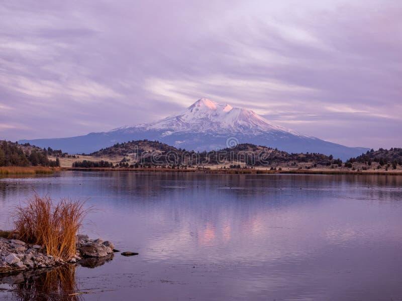 在湖反映的日落的山 库存照片