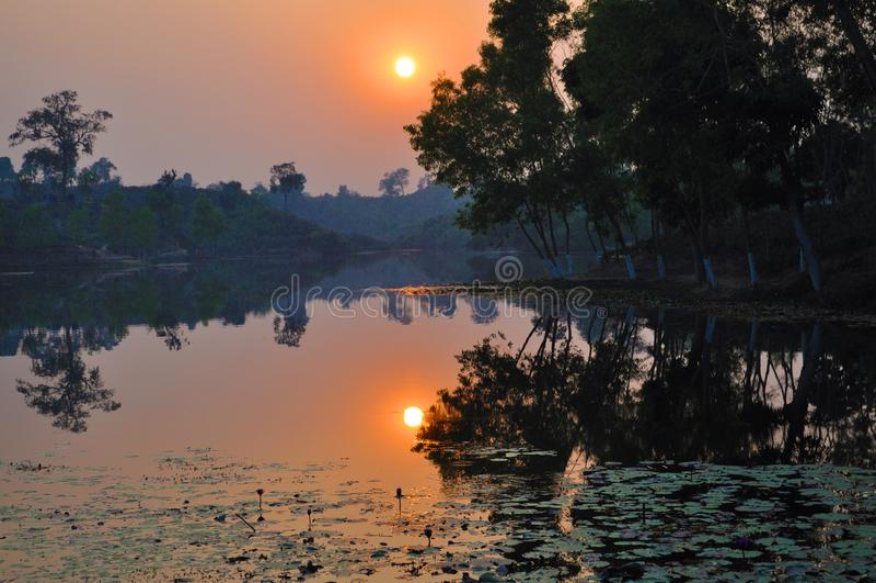 在湖和小山的日落 免版税图库摄影