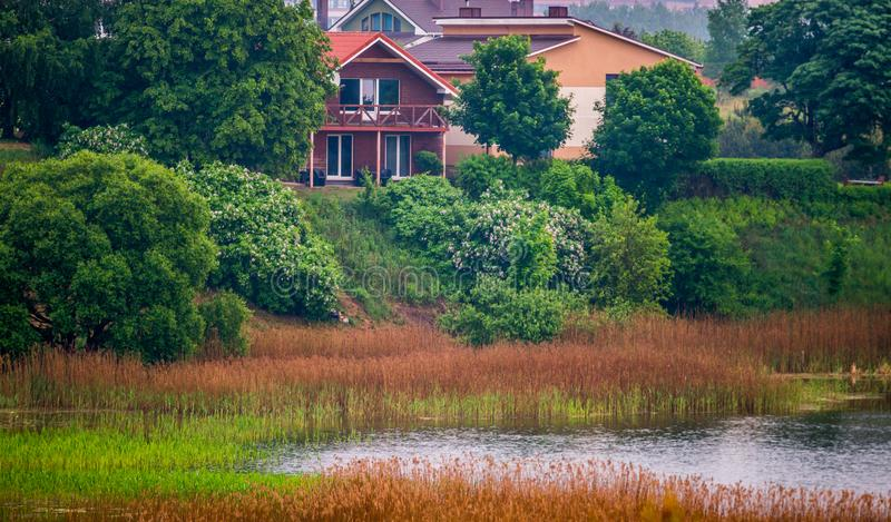 在湖和房子附近的春天风景 库存图片