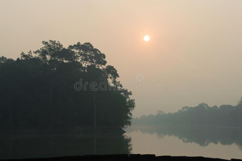 在湖和树的有雾的橙色日出在柬埔寨 免版税库存图片