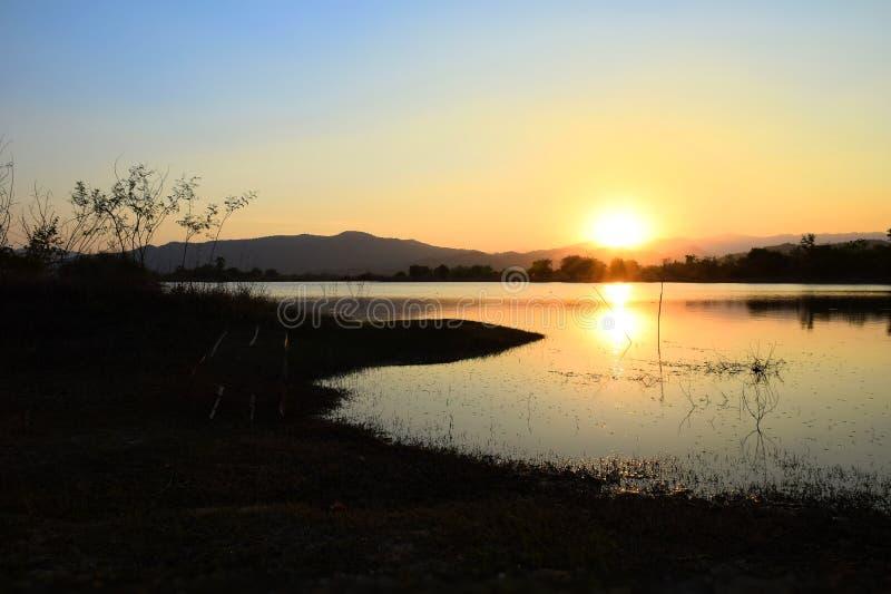在湖山和海的剧烈的日落有Kaeng Krachan水坝,佛丕府泰国雾的  库存照片