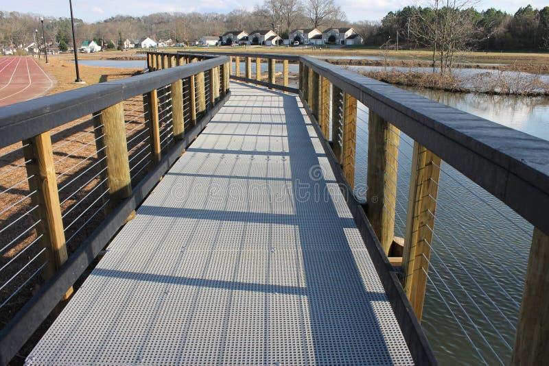 在湖岸狗公园的长和狭窄的桥梁 库存图片