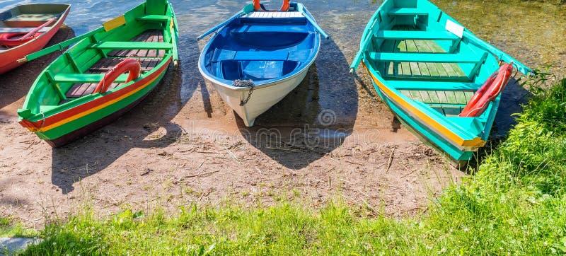 在湖岸的美丽的五颜六色的木小船 库存图片