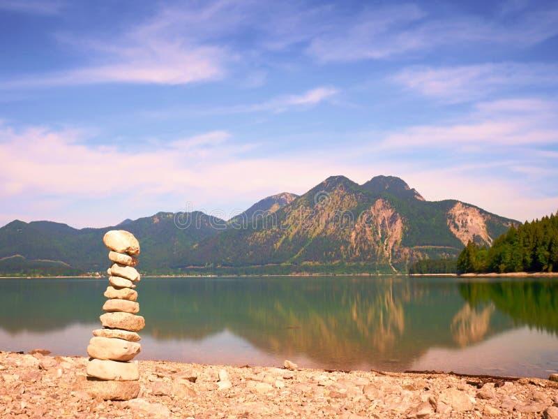 在湖岸的被堆积的小卵石 平衡栈石头 免版税库存图片