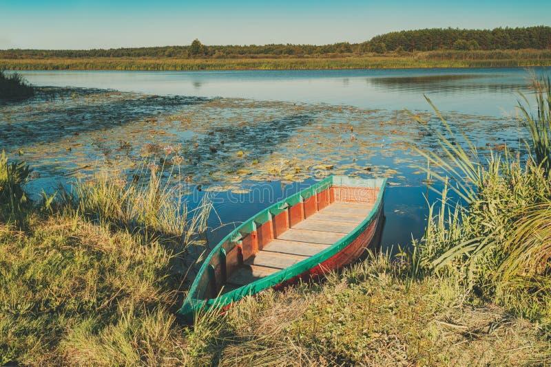 在湖或河海岸附近的老木荡桨的渔船在好漂亮的东西或人 库存照片