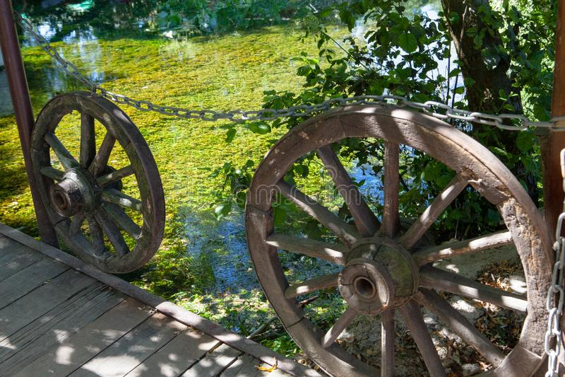 在湖旁边的老木马车车轮 免版税库存图片