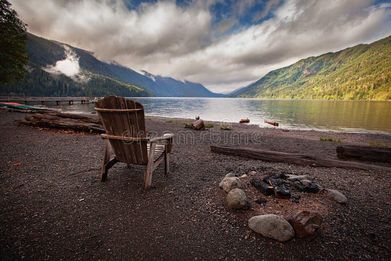 在湖月牙的木椅子 免版税库存图片