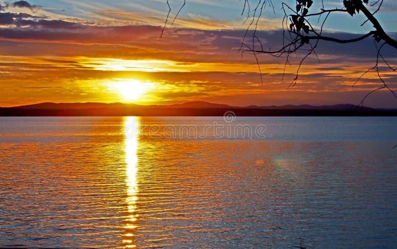 在湖有五颜六色的云彩的,金黄小时的使变暗的日落天空 免版税库存图片