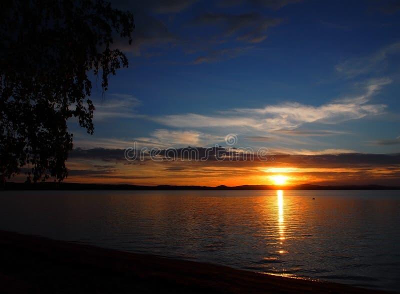 在湖有五颜六色的云彩的,金黄小时的使变暗的日落天空 库存照片
