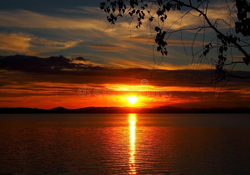 在湖有五颜六色的云彩的,金黄小时的使变暗的日落天空 库存图片