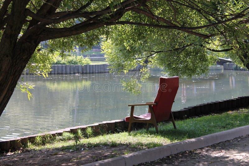在湖的一把老红色扶手椅子在公园,在树的分支下 库存照片