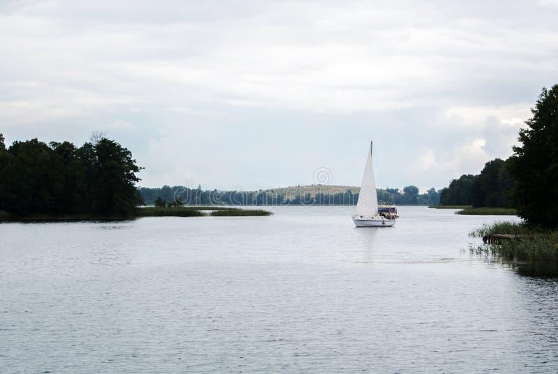 在湖的一艘偏僻的帆船在特拉凯城堡附近 库存照片
