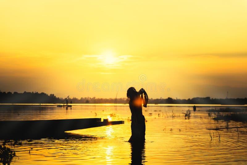 在湖的剪影渔夫人投掷的抄网钓鱼有山和日落天空的 免版税库存照片