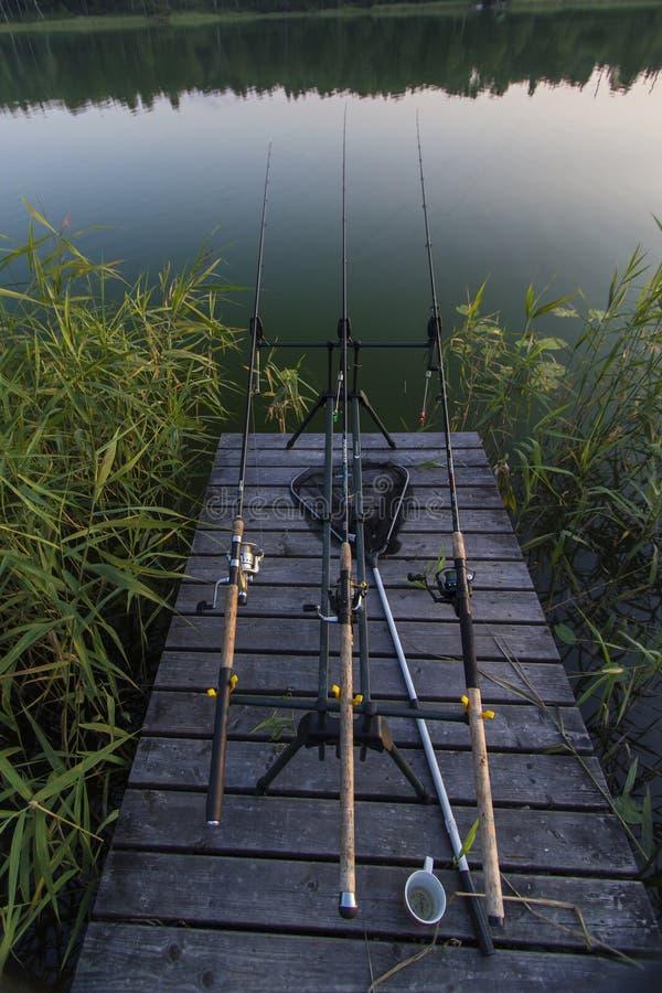 在湖的夏天晚上有钓鱼的在桥梁的路 图库摄影