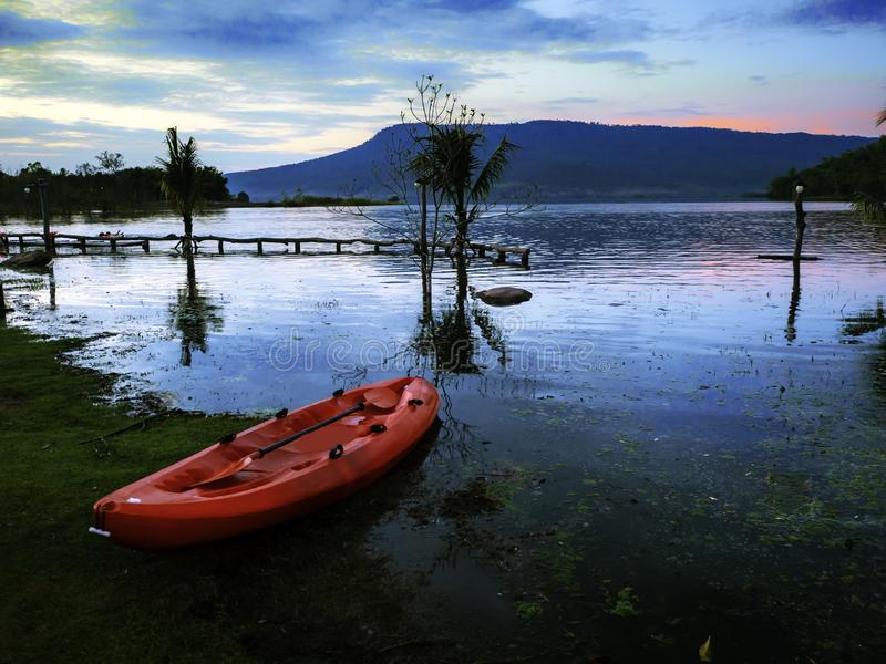 在湖的小渔船沼泽的在晚上,当太阳落时 库存图片