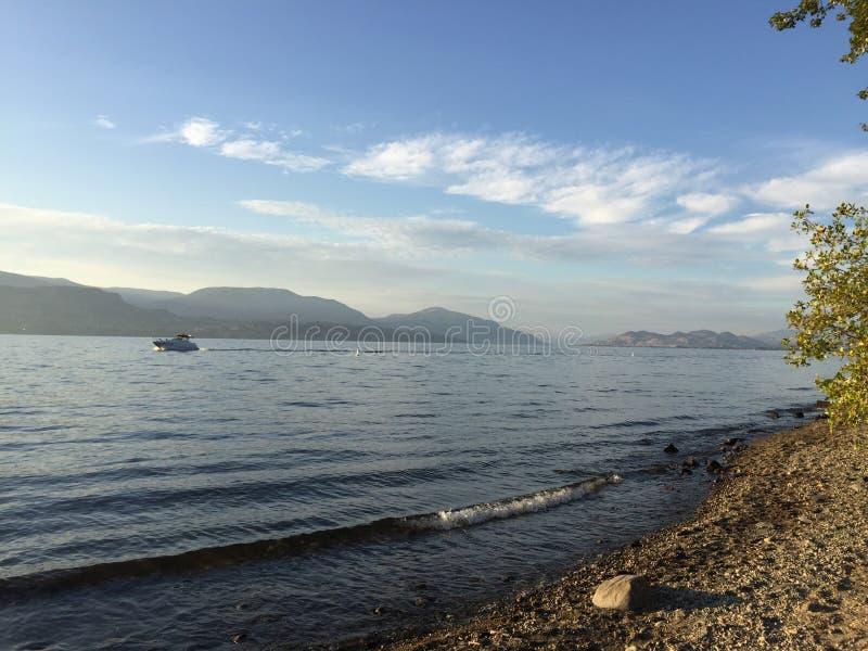 在湖的小船有阴霾和白色云彩的在山 基隆拿, BC 加拿大 图库摄影