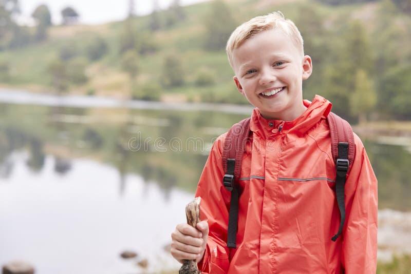 在湖的岸的一个青春期前的男孩身分,查寻对照相机,正面图,腰部,湖区,英国 免版税库存图片