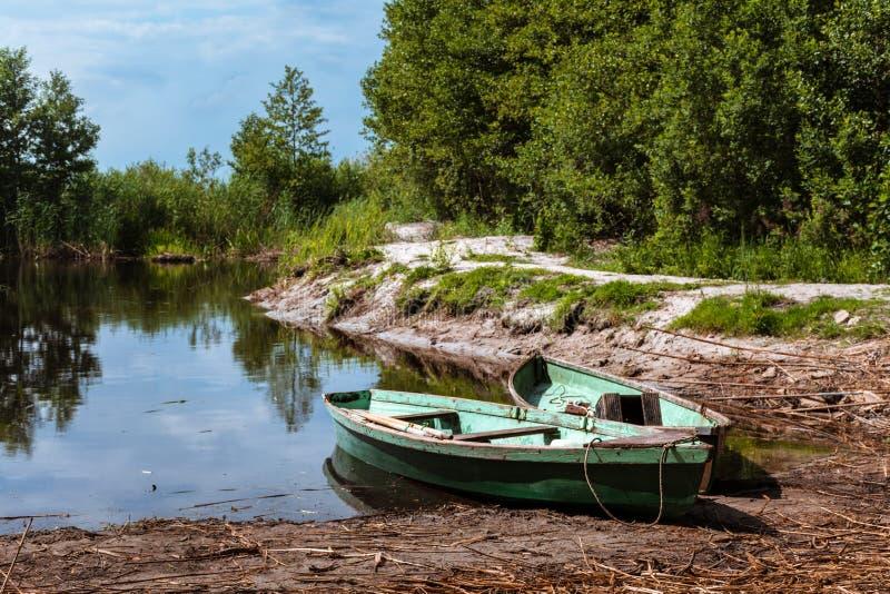 在湖的岸的两个绿色空的渔船 免版税库存照片