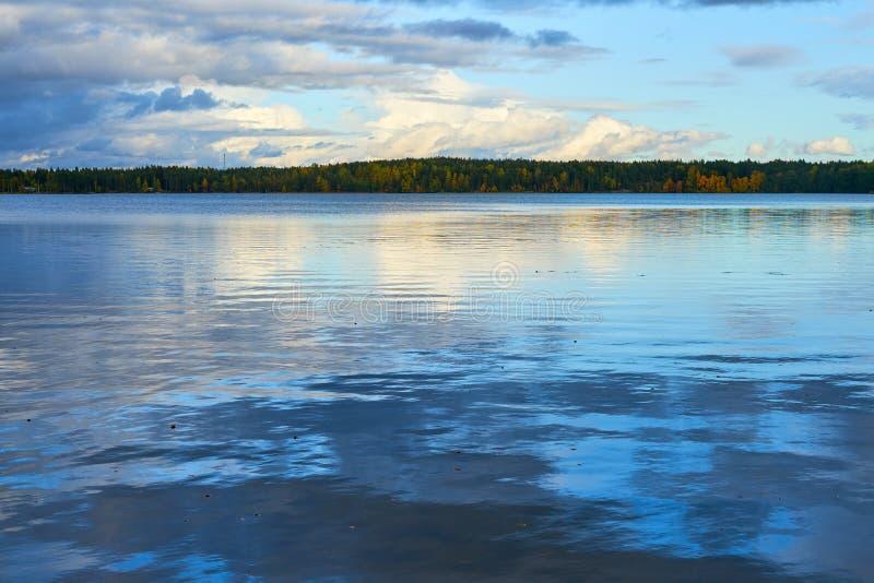 在湖的日落与多云天空的秋天和反射在水中 免版税库存照片