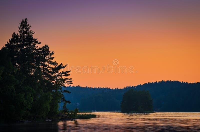 在湖的日落在森林地 免版税库存照片