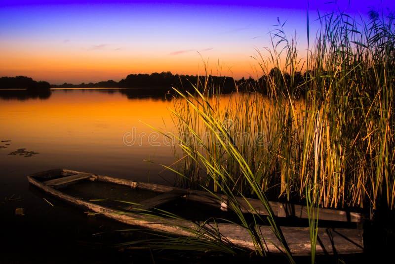 在湖的日落有老小船击毁的 免版税库存图片