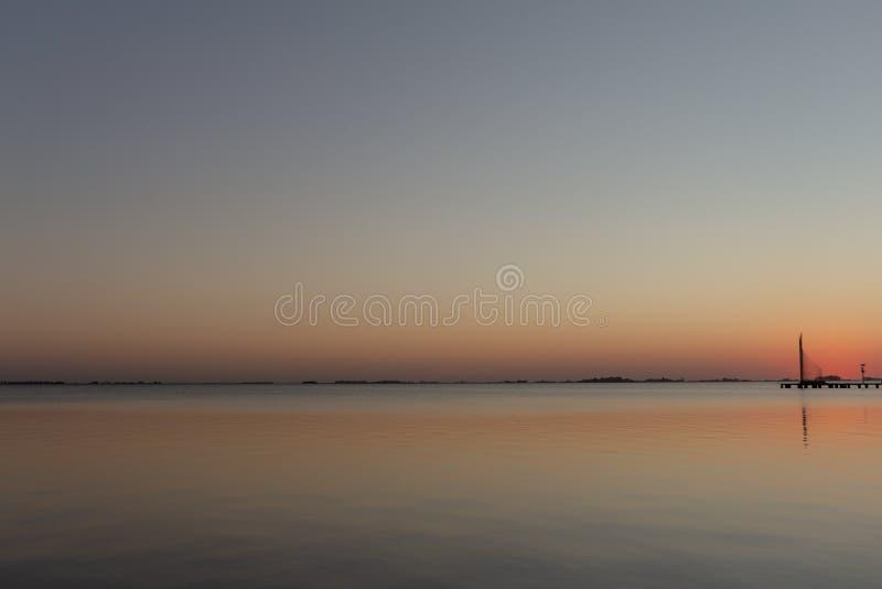 在湖的日落 太阳反射它的在湖的光 桔子和蓝色控制场面 免版税图库摄影
