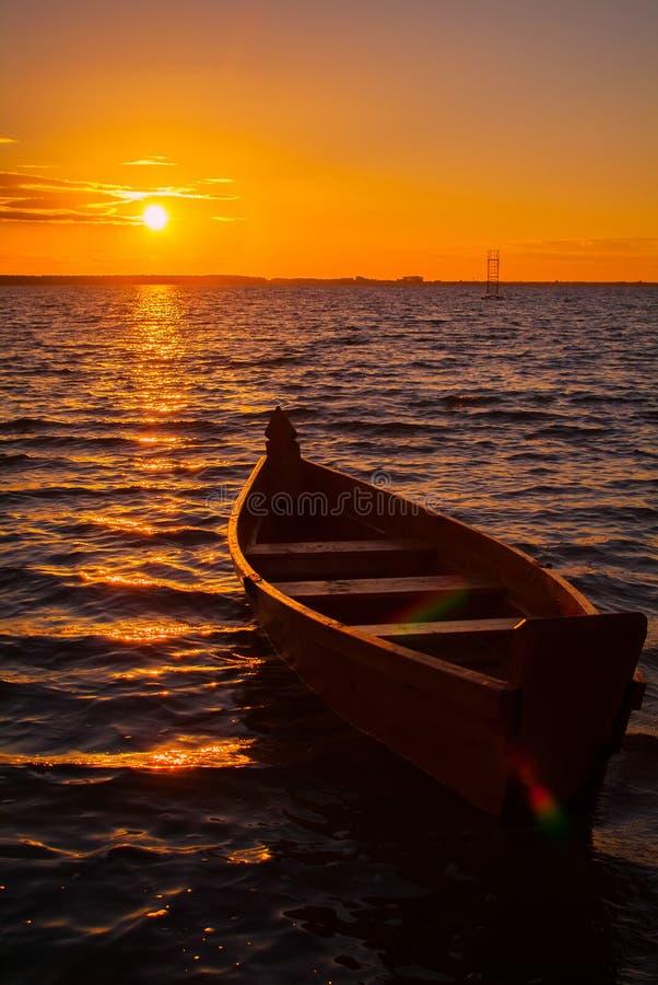 在湖的木小船在日落期间 免版税库存图片
